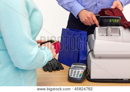 A woman at the store checkout  buying some gifts for a man