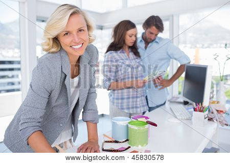Attractive designer looking at the camera while a couple is choosing colours