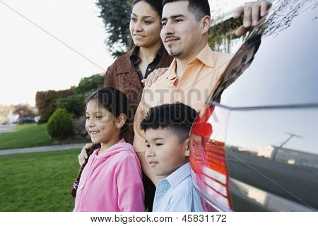 Family standing together beside minivan