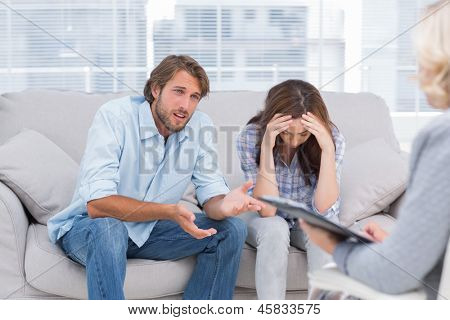 Man speaking to the therapist while her wife cries next to him