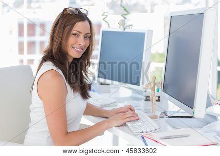 Female designer at her desk smiling at the camera