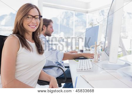 Pretty designer smiling at the camera as her colleague works behind her