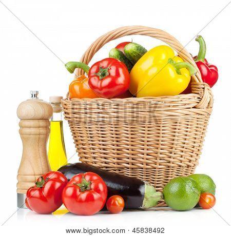 Legumes frescos maduros no cesto com abanador da pimenta e azeite. Isolado no fundo branco