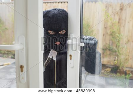 Burglar opening the door with crobar