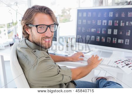 Photo editor viewing thumbnails on computer and turning for portrait at his desk