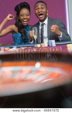 Couple sitting at the table cheering at roulette wheel spinning in the casino