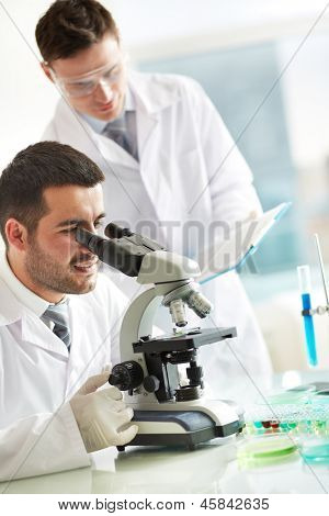 Serious clinician studying chemical element in laboratory with his co-worker standing near by
