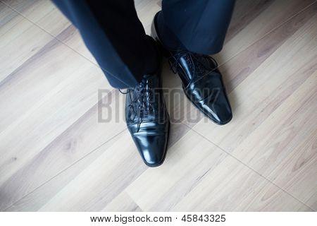 Close-up dos pés do empresário em botas pretas no chão