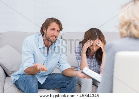 Couple arguing and crying on the couch during therapy session