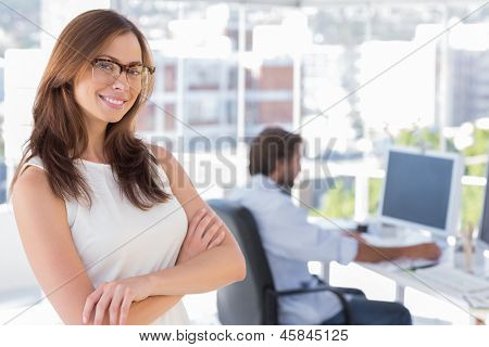 Smiling desginer standing in her office wearing glasses and colleague behind her