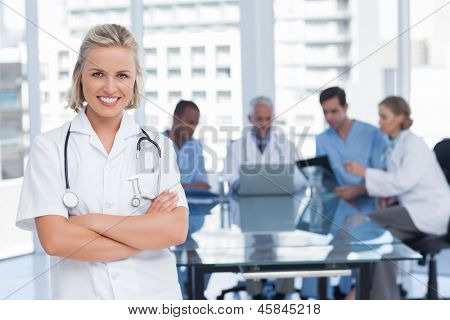 Nurse with arms crossed standing in front of her team