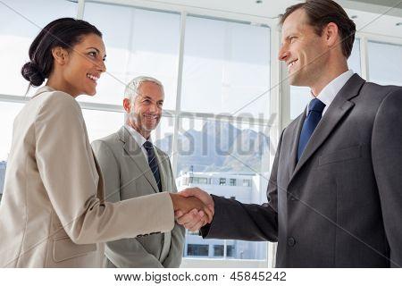Sonriendo empresarios temblando manos con sonriente colega les en el fondo