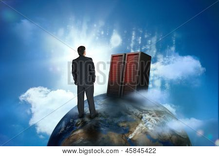 Businessman looking at servers on top of world in bright blue sky