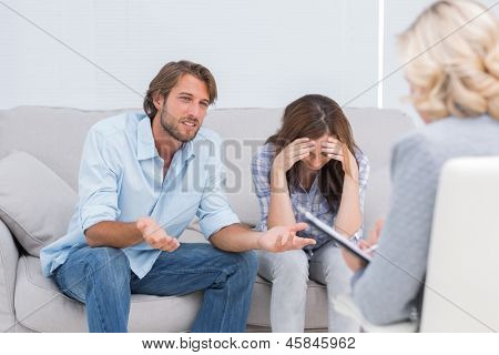 Young couple arguing and crying on the couch during therapy session