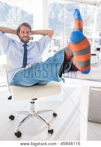 Shoeless designer kicking back at his desk and smiling