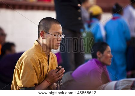 LHASA, TIBET-OCTOBER 08: A Buddhist pilgrim is reading mantra on bended knees in front of the holy Jokhang Monastery on October 08, 2012 in Lhasa, Tibet.
