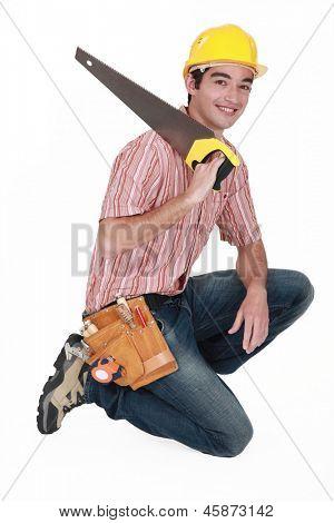 carpenter with saw kneeling