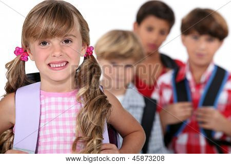 Schulmädchen mit Ranzen und Jungs im Hintergrund