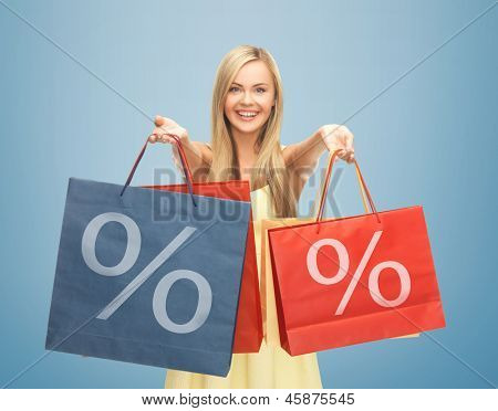 picture of happy woman holding shopping bags with percent sign