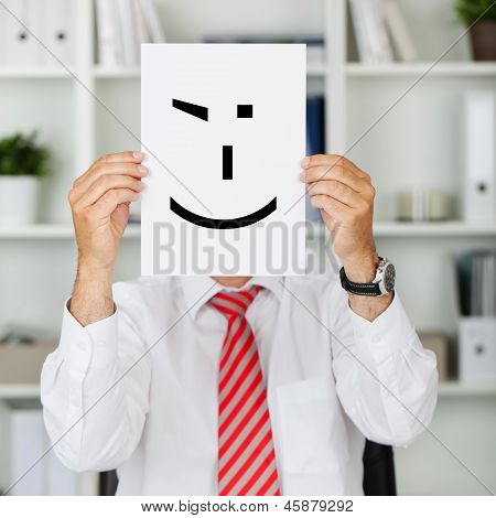 Businessman Holding Wink Smiley In Front Of His Face