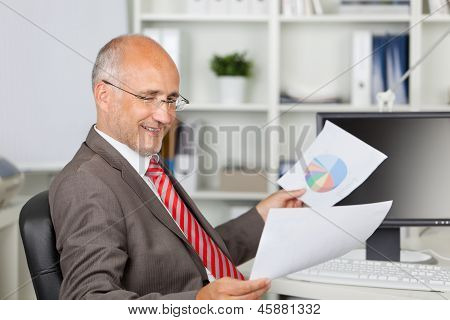 Businessman Analyzing Documents At Office Desk