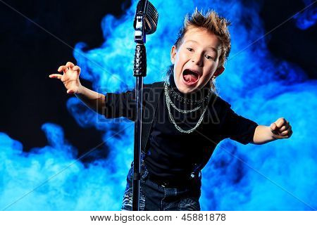 An emotional little boy is singing into a microphone like a rock musician.