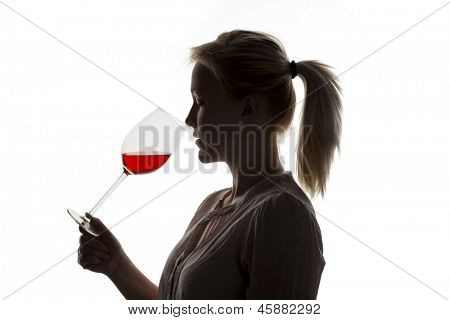 a young woman with a wine tasting. try a glass of red wine in wine glass