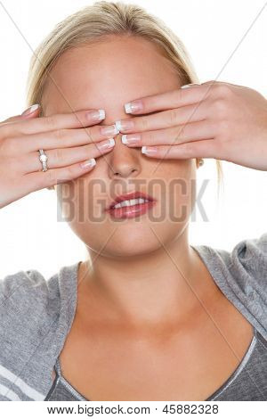 a young woman holding on to the eyes. photo icon for not wanting to see and displacement as well as dispute avoidance
