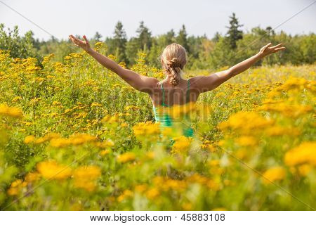 Back Of Woman Practicing Yoga In Meadow Of Yellow Flowers