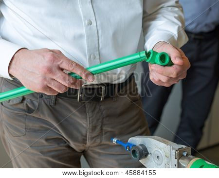 Mechanic working with pipes at workroom
