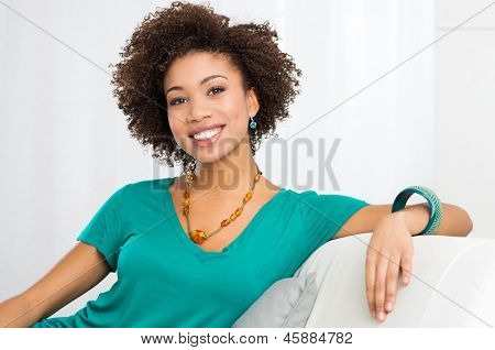 Young Happy Girl Smiling and Sitting On Couch