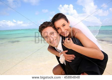 Groom carrying bride on his back at the beach