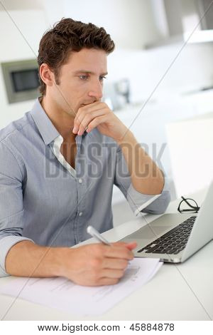Closeup of smart guy working on laptop at home