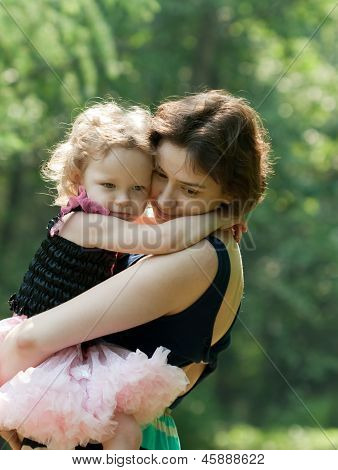 Girl And Her Mother Are Relaxing In The Park