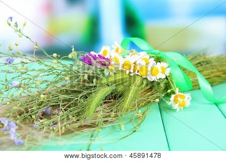 Bouquet of wild flowers and herbs, on wooden table on bright background