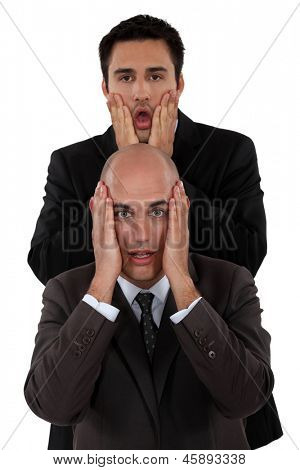 Shocked businessmen making faces