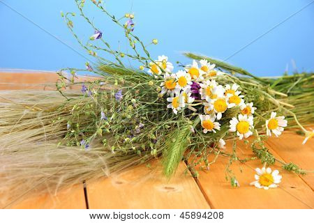 Bouquet of wild flowers and herbs, on wooden table on color background