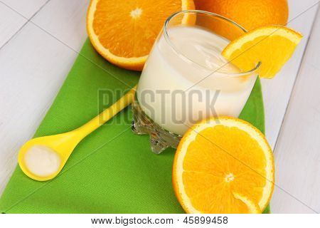 Delicious yogurt in glass with orange on wooden table close-up