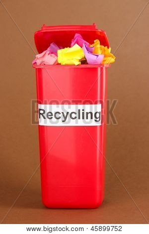 Recycling bin with papers on brown background