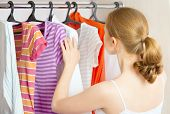 picture of wardrobe  - Young woman chooses clothes in the wardrobe closet at home - JPG
