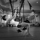 foto of concentration man  - Fitness TRX training exercises at gym woman and man push - JPG
