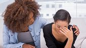 image of comforter  - Sad woman crying next to her therapist who is comforting her - JPG