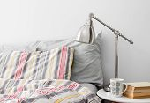 stock photo of pillowcase  - Lamp and books on a side table near bed with colorful bed linen - JPG
