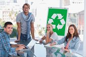 stock photo of take responsibility  - Team having meeting about recycling in bright office - JPG