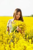 stock photo of beatitudes  - Girl with long hair holding a bouquet of yellow flowers - JPG