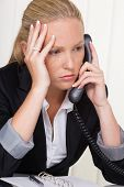 a frustrated woman phoned the office. stress and strain in the workplace.
