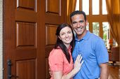 foto of entryway  - Caucasian wife and hispanic husband standing in entryway of home with tall wooden door and windows high ceilings smiling during day - JPG