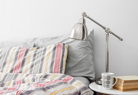 picture of pillowcase  - Lamp and books on a side table near bed with colorful bed linen - JPG