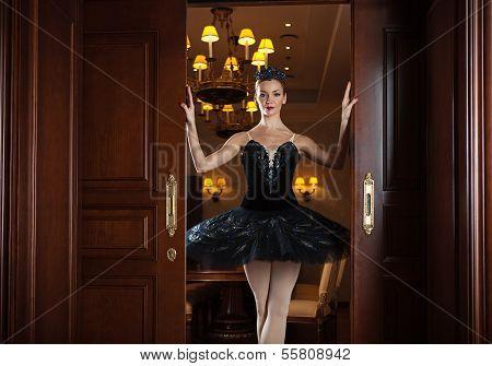 Ballerina in black tutu standing in doorway