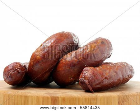 Polish sausage loops on cutting board over white background